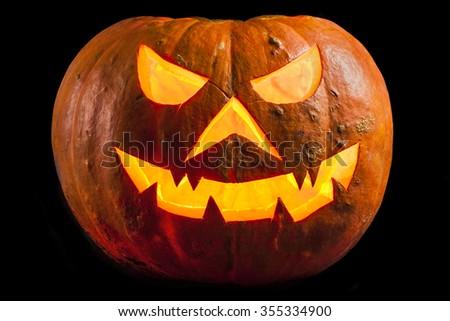 Creepy halloween pumpkin Jack O Lantern shiny inside on black  - stock photo