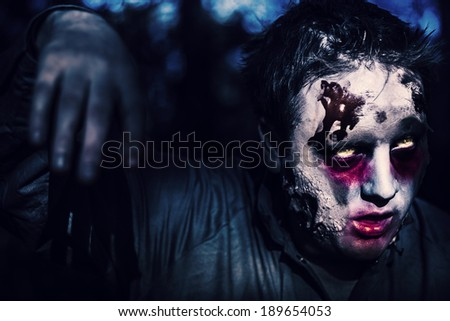 Creepy night photo of a scary zombie looking gravely ill with infectious facial wounds walking through moonlit forest. Attack of the killer monsters