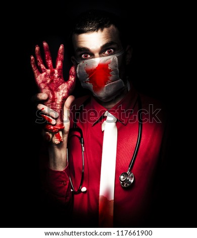 Creepy Psychopathic Pathologist Standing In The Darkness Holding A Sawn Off Hand In A Depiction Of A Autopsy Dissection - stock photo
