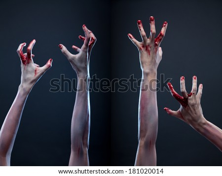 Creepy set of bloody zombie hands, studio shot over gray background   - stock photo