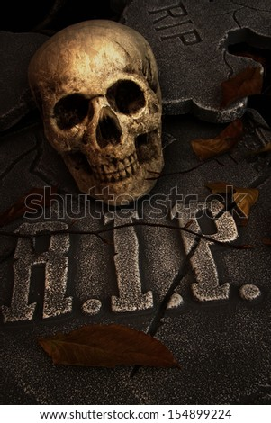 Creepy skull on gravestone in cemetery - stock photo