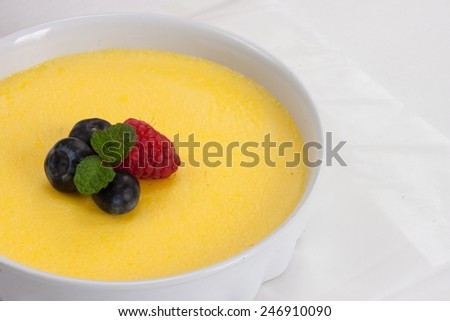 Creme Brulee before caramelization - close up of yellow cream custard in Porcelain ramekin with berries - stock photo