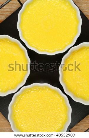 Creme brulee before caramelization - custard yellow cream in porcelain ramekins - stock photo