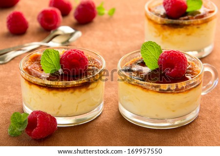 Creme brulee (cream brulee, burnt cream) with raspberries and mint. - stock photo