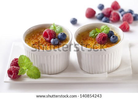 Creme brulee.French vanilla cream dessert with caramelised sugar and berries on top.