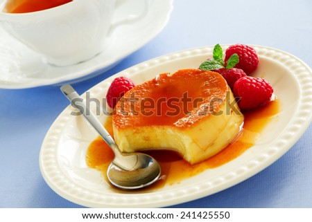 Creme caramel with raspberries. - stock photo