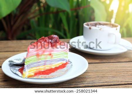 crepe cake and a cup of latte art hot coffee on wood table. - stock photo