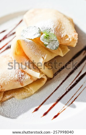 crepe with apple and cinnamon and mint on white plate - stock photo