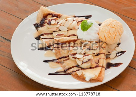 crepe with bananas and ice cream on wood table - stock photo