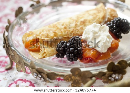 Crepe with whipped cream, blackberries and peaches
