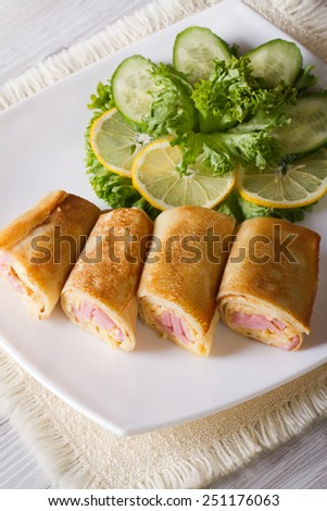 Crepes filled ham and cheese on a white plate. Vertical top view
