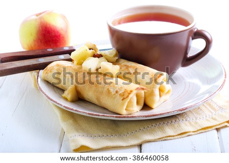 Crepes rolls with spicy apple and raisin filling on plate