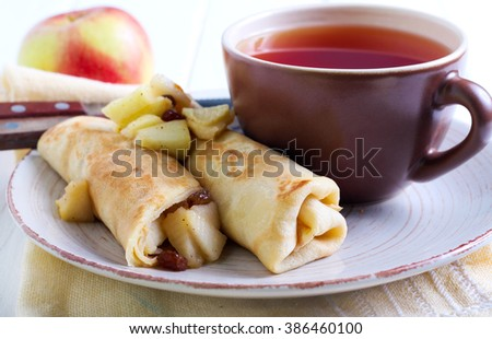 Crepes rolls with spicy apple and raisin filling on plate - stock photo