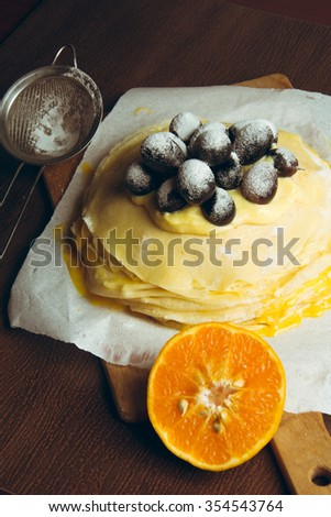 Crepes stuffed with tangerine cream, decorated with grapes