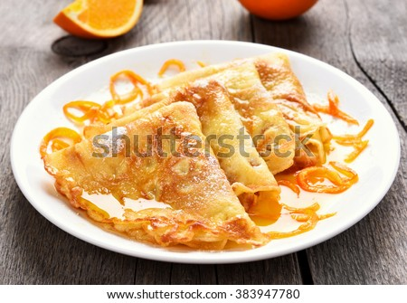 Crepes Suzette on white plate over wooden background - stock photo