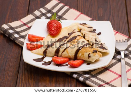 Crepes with Banana, Chocolate and strawberries - stock photo