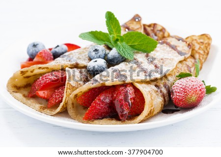 crepes with berries and chocolate sauce, horizontal
