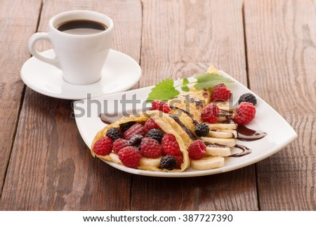 Crepes With Berries and cup of coffee. Crepe with Raspberry, Blueberry and Chocolate topping. - stock photo
