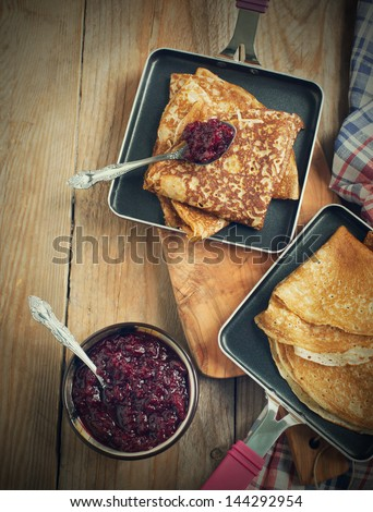 Crepes with black currant jam - stock photo