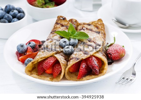 crepes with fresh berries and chocolate sauce for breakfast, closeup, horizontal - stock photo