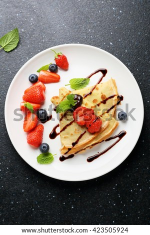 crepes with fresh berries and sauce, food top view - stock photo
