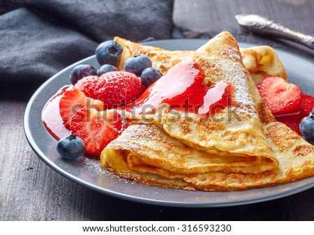 crepes with fresh berries and sweet sauce on dark wooden table - stock photo