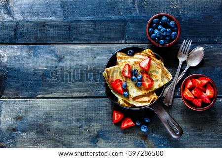 Crepes with fresh berries on rustic wooden background with space for text, top view. Pancake. - stock photo