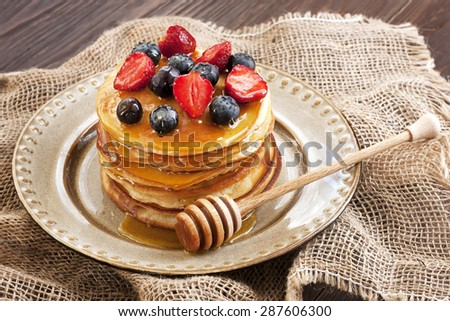 Crepes with  fresh berries. Pancakes stack with strawberry, blueberry and honey - stock photo