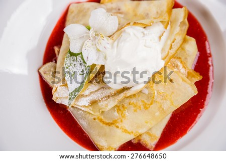 Crepes with ice-cream and strawberry jam - stock photo