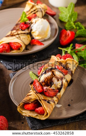 Crepes with ice cream, caramel topping and strawberries. Delicious homemade caramel creame - stock photo