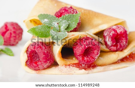 Crepes with raspberries  on a white plate - stock photo
