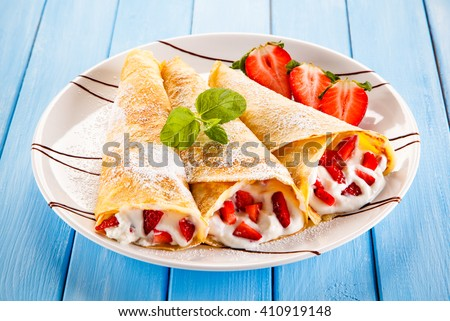 Crepes with strawberries and cream  - stock photo