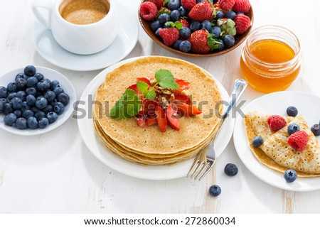 crepes with strawberries and honey for breakfast, top view - stock photo