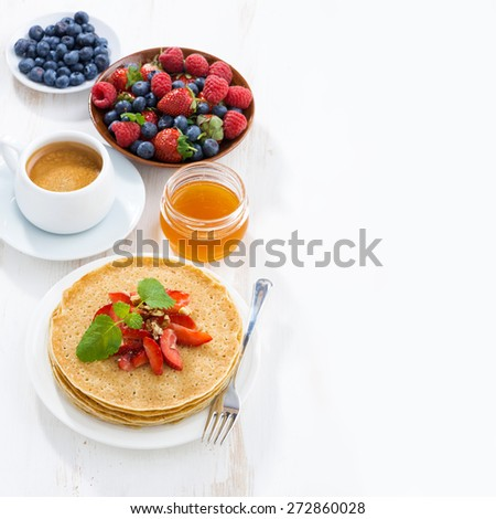 crepes with strawberries and honey for breakfast, white wooden background, top view - stock photo