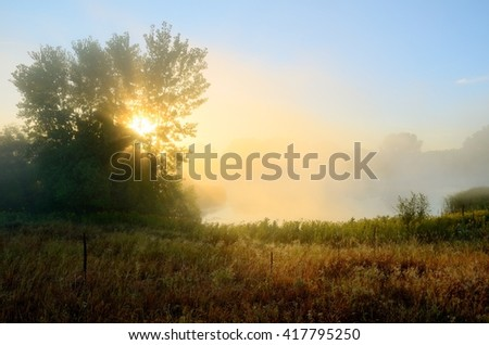 Crepuscular Rays Through the Fog Near a Pond by the Rice Creek North Regional Trail in Shoreview, Minnesota - stock photo