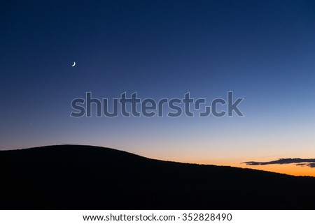 Crescent Moon at Sunset with Colorful Sky - stock photo