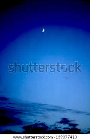 crescent moon with beautiful sunset background - stock photo