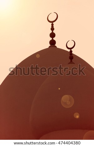 Crescent moons of the Islamic faith on the domes of a mosque. Added lens flare and vintage filter.