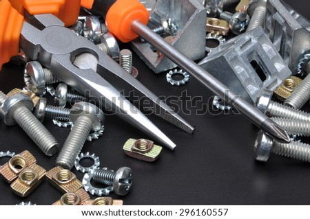 Crescent wrench screws and bolts on black metal surface