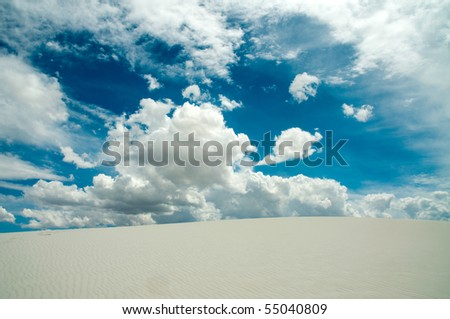 crest of a sandy hill and bright blue cloudy sky - stock photo