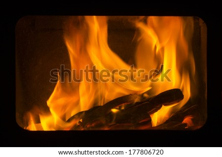 Crest of flame on burning wood in fireplace - stock photo