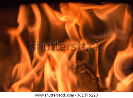 crest of flame on burning wood in stove for background