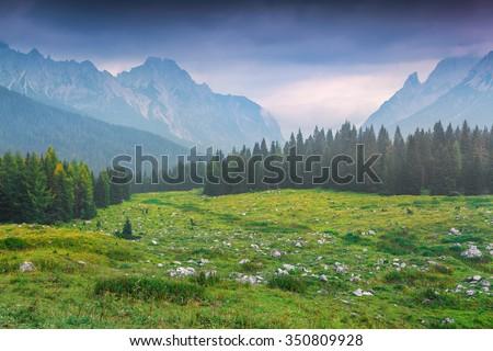 Cresta di Enghe mountain range at foggy summer morning. Dolomites mountains, Italy, Europe. - stock photo