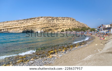 CRETE,GREECE-AUGUST 20: People on Matala beach with the caves on Libyan sea on August 20, 2013 Crete, Greece.