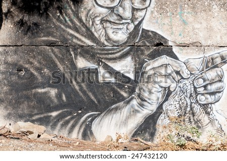 CRETE, GREECE - SEPTEMBER 13. Knitting grandma as graffiti on wall on the old road to Rethymnon on September 13, 2014.