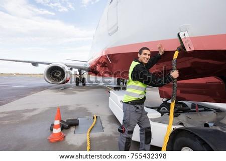 Crew Member Charging Airplane On Runway