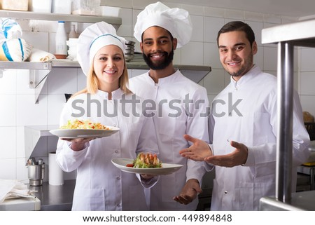 Crew of positive professional cooks working at restaurant kitchen