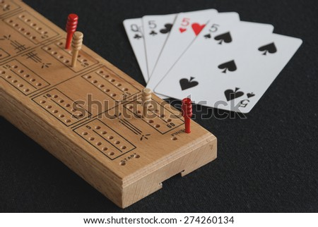 Cribbage board and winning hand, selective focus on the peg that has crossed the finish - stock photo