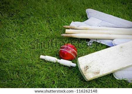 cricket ball, bat & pads with stumps and bail on grass - stock photo