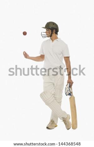 Cricket batsman tossing a cricket ball - stock photo